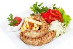 Ψημένα στη σχάρα λουκάνικα με τις τηγανιτές πατάτες, sauerkraut και Στοκ Εικόνες