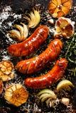 Ψημένα στη σχάρα λουκάνικα με το σκόρδο και τα κρεμμύδια προσθηκών Στοκ εικόνα με δικαίωμα ελεύθερης χρήσης