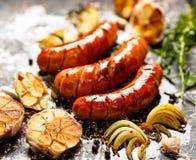 Ψημένα στη σχάρα λουκάνικα με το σκόρδο και τα κρεμμύδια προσθηκών Στοκ εικόνες με δικαίωμα ελεύθερης χρήσης