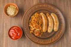 Ψημένα στη σχάρα λουκάνικα με sauerkraut, μουστάρδας και ντοματών τη σάλτσα κορυφαία όψη Στοκ εικόνες με δικαίωμα ελεύθερης χρήσης