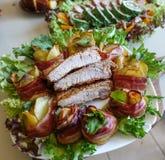 Ψημένα στη σχάρα πλευρά χοιρινού κρέατος σε ένα άσπρο πιάτο με τα πράσινα, το μαρούλι και τους ρόλους κρέατος στοκ φωτογραφίες με δικαίωμα ελεύθερης χρήσης