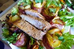 Ψημένα στη σχάρα πλευρά χοιρινού κρέατος σε ένα άσπρο πιάτο με τα πράσινα, το μαρούλι και τους ρόλους κρέατος στοκ εικόνα