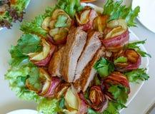 Ψημένα στη σχάρα πλευρά χοιρινού κρέατος σε ένα άσπρο πιάτο με τα πράσινα, το μαρούλι και τους ρόλους κρέατος στοκ εικόνες
