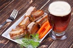 Ψημένα στη σχάρα πλευρά χοιρινού κρέατος και ποτήρι της μπύρας Στοκ εικόνα με δικαίωμα ελεύθερης χρήσης