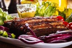 Ψημένα στη σχάρα πλευρά χοιρινού κρέατος με τα φρέσκα λαχανικά και μουστάρδα σε ένα πιάτο Στοκ εικόνες με δικαίωμα ελεύθερης χρήσης