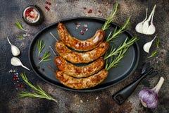 Ψημένα στη σχάρα σπιτικά οβελίδια λουκάνικων δεντρολιβάνου στο τηγανίζοντας τηγάνι σιδήρου πέρα από τον αγροτικό σκοτεινό πίνακα  Στοκ Εικόνες