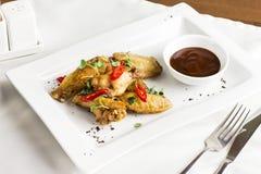 Ψημένα στη σχάρα ψημένα φτερά κοτόπουλου με το πιπέρι τσίλι και την καυτή σάλτσα Στοκ φωτογραφία με δικαίωμα ελεύθερης χρήσης
