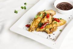 Ψημένα στη σχάρα ψημένα φτερά κοτόπουλου με το πιπέρι τσίλι και την καυτή σάλτσα Στοκ εικόνα με δικαίωμα ελεύθερης χρήσης