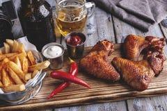 Ψημένα στη σχάρα φτερά κοτόπουλου, τηγανιτές πατάτες, άσπρα και κόκκινα καρύδια σάλτσας σε μια ξύλινη επιφάνεια Μπουκάλι και ποτή στοκ εικόνες