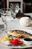 Ψημένα στη σχάρα ψάρια με την ντομάτα, τα χορτάρια, τα κρεμμύδια και το λεμόνι Στοκ εικόνες με δικαίωμα ελεύθερης χρήσης