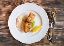 Ψημένα στη σχάρα ψάρια με τη φέτα του λεμονιού και του άσπρου sause στο ξύλινο backg Στοκ εικόνα με δικαίωμα ελεύθερης χρήσης
