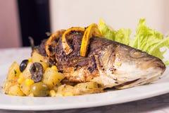 Ψημένα στη σχάρα ψάρια σε ένα πιάτο με το λεμόνι και τα λαχανικά στοκ φωτογραφία