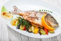 Ψημένα στη σχάρα ψάρια dorado με τα ψημένα λαχανικά και δεντρολίβανο στο πιάτο στο ξύλινο υπόβαθρο κοντά επάνω στοκ φωτογραφία