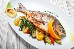 Ψημένα στη σχάρα ψάρια dorado με τα ψημένα λαχανικά και δεντρολίβανο στο πιάτο στο ξύλινο υπόβαθρο κοντά επάνω στοκ φωτογραφία με δικαίωμα ελεύθερης χρήσης