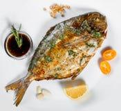 Ψημένα στη σχάρα ψάρια dorado με τα πράσινα και λεμόνι στο μαύρο υπόβαθρο που απομονώνεται στοκ φωτογραφίες