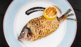 Ψημένα στη σχάρα ψάρια dorado με τη σάλτσα λεμονιών και τρουφών στο πιάτο στο ξύλινο υπόβαθρο Εύγευστο πιάτο των θαλασσινών στοκ εικόνα με δικαίωμα ελεύθερης χρήσης