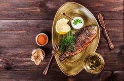 Ψημένα στη σχάρα ψάρια dorado με το λεμόνι και πράσινα στο πιάτο στο ξύλινο υπόβαθρο Εύγευστο πιάτο των θαλασσινών στοκ εικόνες