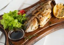 Ψημένα στη σχάρα ψάρια & x28 Dorado& x29  σε έναν ξύλινο πίνακα με τις ντομάτες λεμονιών, σαλάτας, σάλτσας και κερασιών Στοκ Εικόνα
