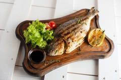 Ψημένα στη σχάρα ψάρια & x28 Dorado& x29  σε έναν ξύλινο πίνακα με τις ντομάτες λεμονιών, σαλάτας, σάλτσας και κερασιών Στοκ φωτογραφία με δικαίωμα ελεύθερης χρήσης