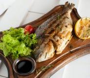 Ψημένα στη σχάρα ψάρια & x28 Dorado& x29  σε έναν ξύλινο πίνακα με τις ντομάτες λεμονιών, σαλάτας, σάλτσας και κερασιών Στοκ φωτογραφίες με δικαίωμα ελεύθερης χρήσης
