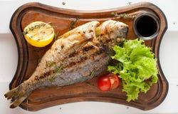 Ψημένα στη σχάρα ψάρια & x28 Dorado& x29  σε έναν ξύλινο πίνακα με τις ντομάτες λεμονιών, σαλάτας, σάλτσας και κερασιών Στοκ Εικόνες