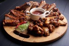 Ψημένα τεμαχισμένα πλευρά χοιρινού κρέατος σχαρών με τα φτερά κοτόπουλου και τα αρωματικά χορτάρια και souce στοκ φωτογραφίες