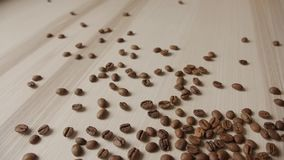 Ψημένα φασόλια καφέ που ανατρέπουν έξω στην ξύλινη σανίδα απόθεμα βίντεο