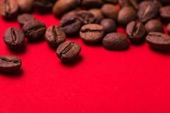 Ψημένα φασόλια καφέ στο κόκκινο υπόβαθρο Τάση κύματος χρώματος Στοκ Εικόνα