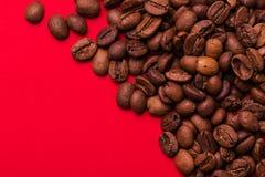 Ψημένα φασόλια καφέ στο κόκκινο υπόβαθρο Τάση κύματος χρώματος Στοκ Φωτογραφία