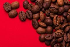 Ψημένα φασόλια καφέ στο κόκκινο υπόβαθρο Τάση κύματος χρώματος Στοκ φωτογραφία με δικαίωμα ελεύθερης χρήσης