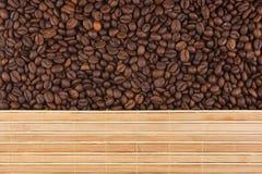 Ψημένα φασόλια καφέ και ένα χαλί μπαμπού Στοκ Φωτογραφίες