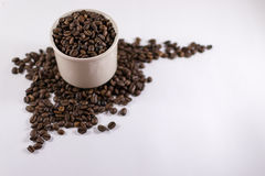 Ψημένα φασόλια καφέ μέσα σε ένα φλυτζάνι με Copyspace στο άσπρο χαρτόνι στοκ φωτογραφία