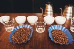 Ψημένα φασόλια καφέ με τα φλυτζάνια έτοιμα για μια δοκιμή Στοκ Εικόνες