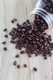 Ψημένα φασόλια καφέ που ανατρέπονται από το βάζο κτιστών στον ξύλινο κατασκευασμένο πίνακα Στοκ Εικόνες
