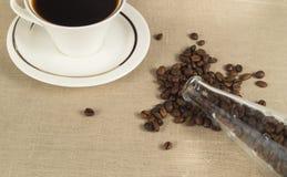 Ψημένα φασόλια καφέ σε ένα μπουκάλι γυαλιού και ένα φλιτζάνι του καφέ στο ύφασμα λινού στοκ φωτογραφία με δικαίωμα ελεύθερης χρήσης