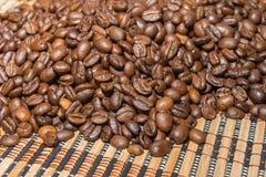 Ψημένα φασόλια καφέ σε ένα χαλί μπαμπού Στοκ Εικόνες