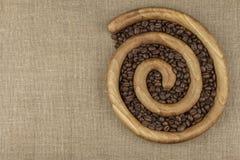 Ψημένα φασόλια καφέ σε μια ξύλινη σπείρα στο υπόβαθρο καμβά φρέσκος καφέ που ψήνεται Στοκ Εικόνα