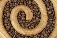 Ψημένα φασόλια καφέ σε μια ξύλινη σπείρα στο υπόβαθρο καμβά φρέσκος καφέ που ψήνεται Στοκ Φωτογραφία