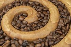Ψημένα φασόλια καφέ σε μια ξύλινη σπείρα στο υπόβαθρο καμβά φρέσκος καφέ που ψήνεται Στοκ Εικόνες