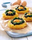 Ψημένα φούρνος αυγά στις φωλιές πατατών και σπανακιού στοκ φωτογραφίες