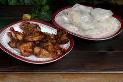 Ψημένα φτερά κοτόπουλου με το κολλώδες ρύζι στον ξύλινο πίνακα στοκ φωτογραφίες