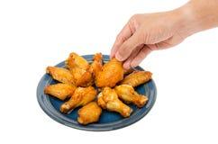 ψημένα φτερά κοτόπουλου με το χέρι ατόμων στοκ φωτογραφία