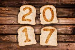 ψημένες ευχετήρια κάρτα φέτες του 2017 του ψωμιού στο ξύλινο υπόβαθρο σανίδων Στοκ Εικόνα