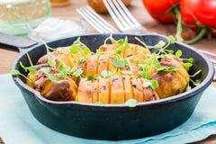 Ψημένες νέες πατάτες στα καρυκεύματα και έλαιο με το arugula σε ένα τηγάνι Στοκ Φωτογραφίες