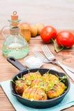 Ψημένες νέες πατάτες στα καρυκεύματα και έλαιο με το arugula σε ένα τηγάνι Στοκ Εικόνες