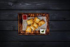 Ψημένες πίτες με την ξινές κρέμα και τη σάλτσα σε έναν ξύλινο πίνακα Τοπ όψη Μαύρη ξύλινη ανασκόπηση Στοκ εικόνα με δικαίωμα ελεύθερης χρήσης