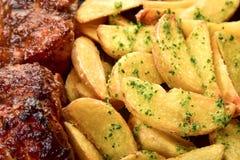 Ψημένες πατάτες με πράσινα καρυκευμάτων και δύο κομμάτια του κρέατος στοκ εικόνες με δικαίωμα ελεύθερης χρήσης