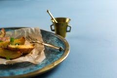 Ψημένες πατάτες με τα πράσινα κρεμμύδια, γαλαζωπό υπόβαθρο στοκ εικόνες
