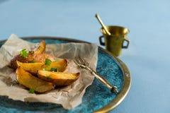 Ψημένες πατάτες με τα πράσινα κρεμμύδια, γαλαζωπό υπόβαθρο στοκ φωτογραφίες