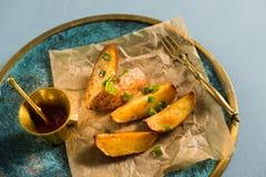 Ψημένες πατάτες με τα πράσινα κρεμμύδια, γαλαζωπό υπόβαθρο στοκ φωτογραφίες με δικαίωμα ελεύθερης χρήσης